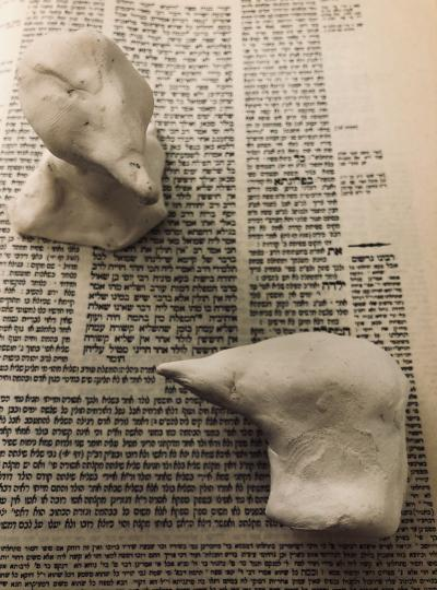 2 raven sculptures against Hebrew text